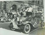 American Legion members riding in decorated car in parade
