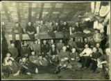 Group portrait of logging crew inside bunkhouse, 1900-1920