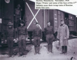 Major Charles M. Winter and members fo the 27th infantry in front of Red Cross box cars, Harbin,...