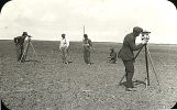 Crew of men using surveying equipment on tilled field